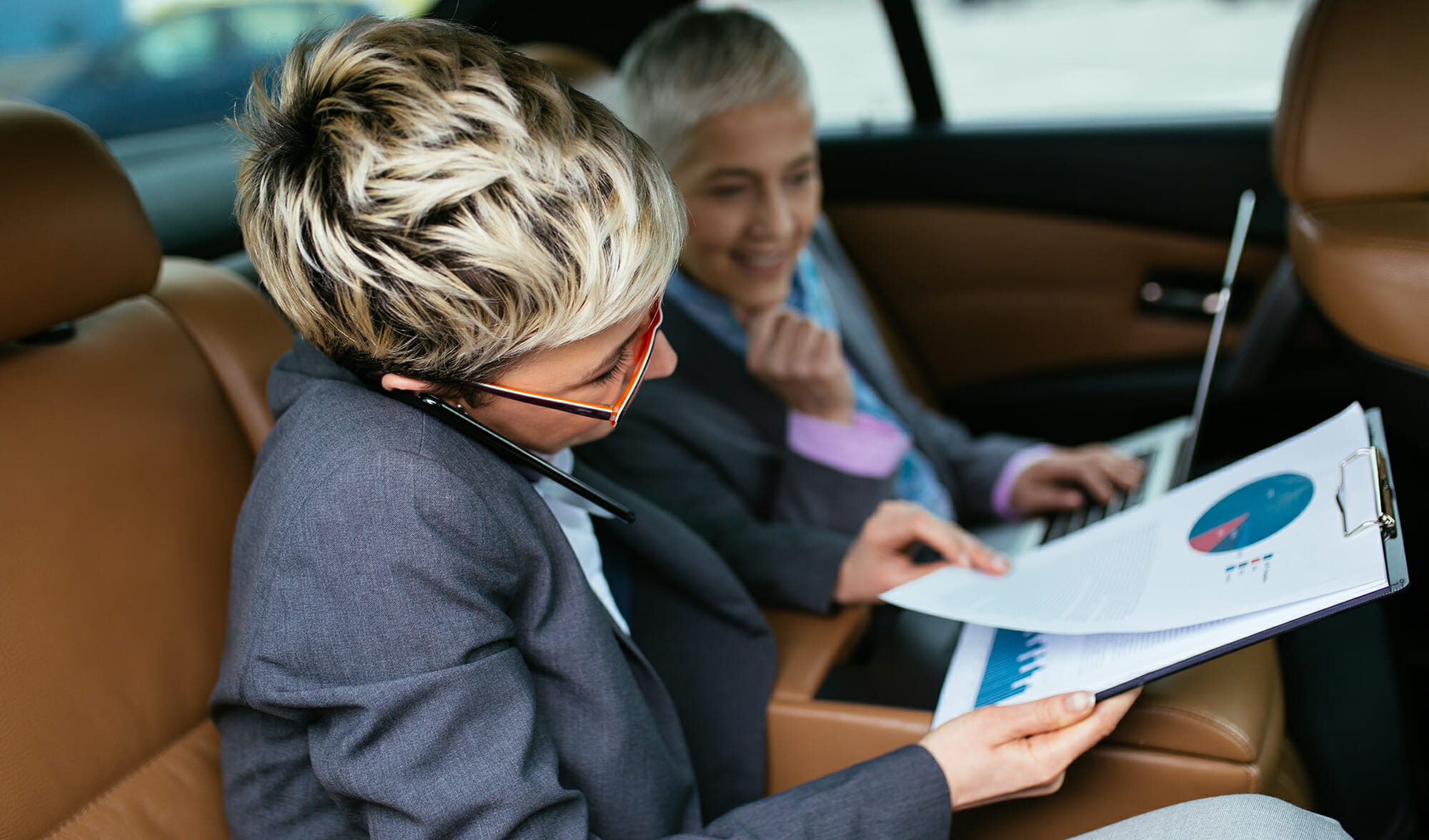 Senior businesswoman and her assistant sitting in limousine talk